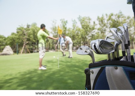 Three friends playing golf on the golf course - stock photo