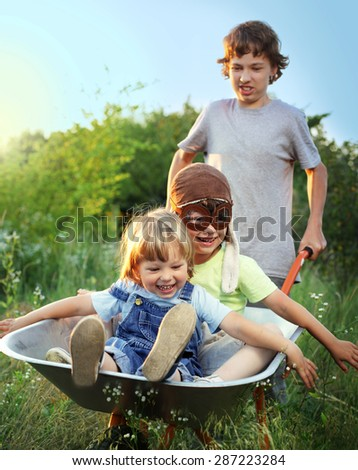 three friends playing in the plane using a garden carts (focus only on child in cart) - stock photo