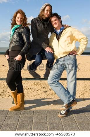 Three friends posing on the boulevard near a beach on a beautiful sunny autumn afternoon - stock photo