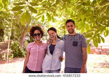 Three friends posing with toothy smiles in the dappled shade of a tree wearing casual clothing and looking at the camera