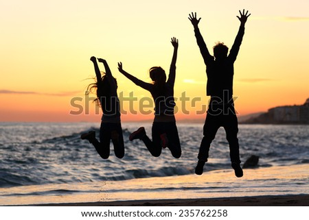 Three friends silhouettes jumping happy and raising arms on the beach at sunset - stock photo