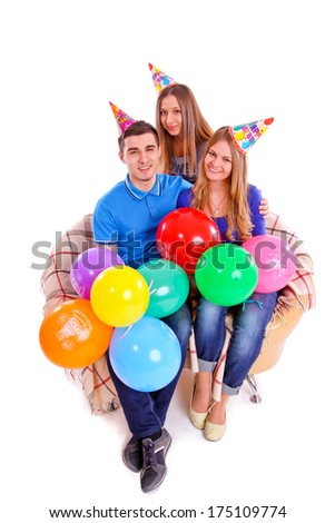 Three friends sitting on a couch with hats and balloons isolated - stock photo