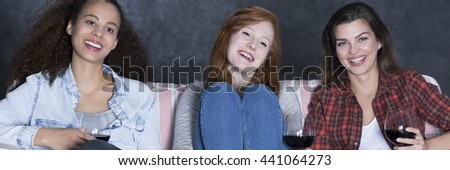 Three friends sitting on a sofa at evening, smiling and drinking wine, panorama