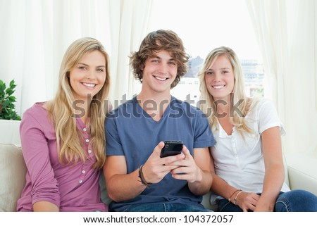 Three friends sitting together looking at the camera with  a mobile phone
