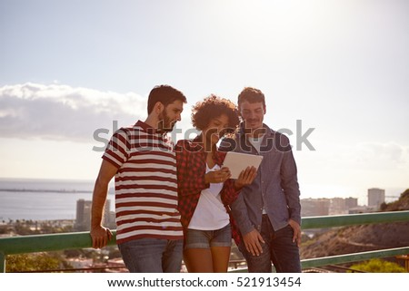 Three friends smiling at a tablet with very bright late afternoon sun behind them and a city scape and bay area