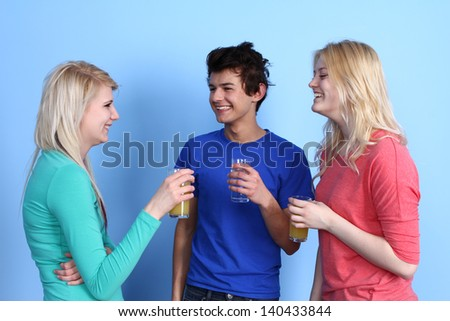 Three friends socialising with non alcoholic drinks against a blue background.