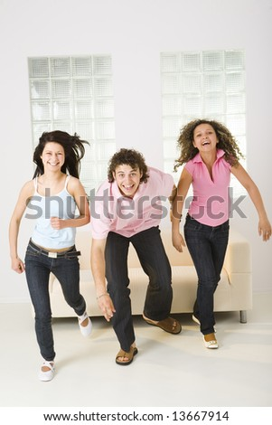 Three friends stood up from couch and started run. They're smiling and  looking at camera. Front view. - stock photo