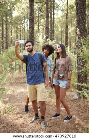 Three friends taking a selfie in a pine tree forest in the late afternoon shadows in front of a tree while wearing casual clothing