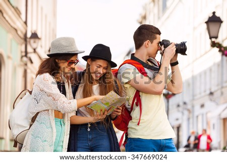 Three friends together with city map and camera