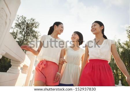 Three Friends Walking Across a Bridge - stock photo