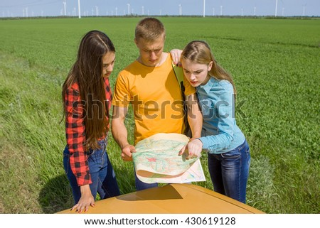 Three friends wanderer searching direction on location map on old car, two girls and  guy tourist searching road to hotel or direction seaon atlas in country road