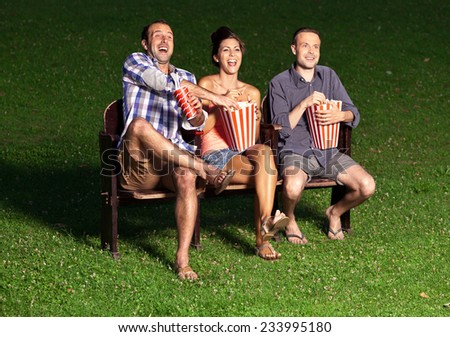 three friends watching a movie at cinema outdoors - stock photo