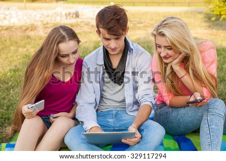 Three friends watching funny movies on tablet pc in park