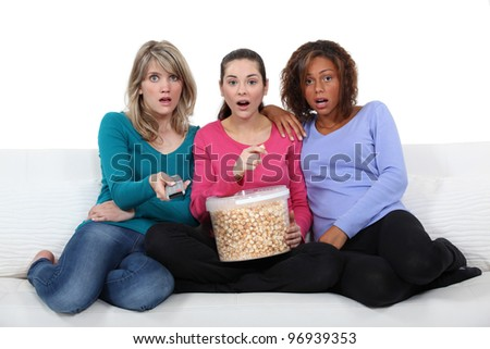 three friends watching television and eating popcorn