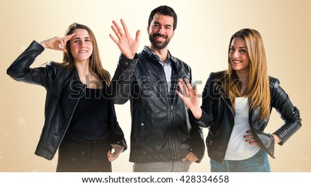 Three friends with black leather saluting