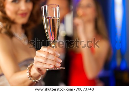 Three friends with champagne in a bar, a woman is looking in the camera; focus on glass in front - stock photo