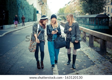 three friends woman on the phone in the street - stock photo