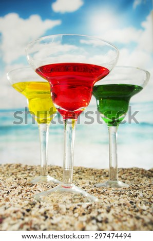 three fruity cocktails red yellow green on the sand with the sea in the background beach - stock photo