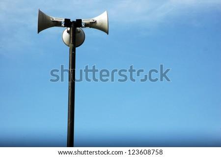 three funnel loudspeakers against blue sky - stock photo