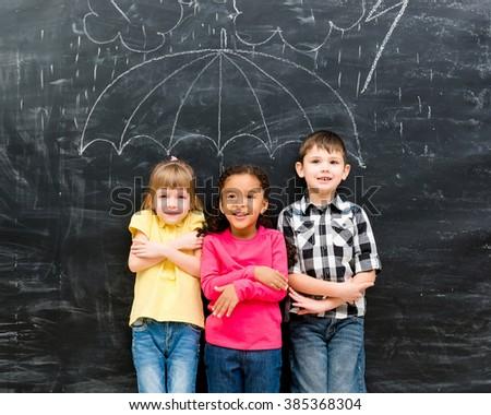 three funny children standing under drawn on blackboard umbrella  - stock photo