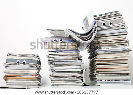Three funny looking stacks of magazines with googly eyes against a white background.