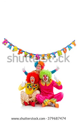 """Three funny playful clowns showing OK sign, in the background hanging """"Happy birthday"""" garland, isolated on a white. - stock photo"""