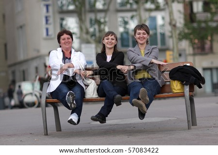 Three funny woman on a bench in city - stock photo