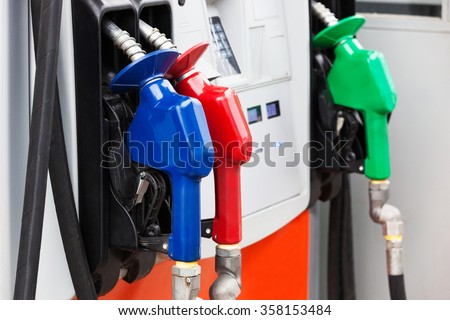three gas hoses on a modern gas station - stock photo