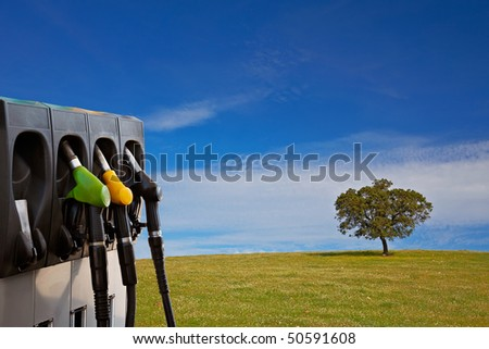 Three gas pump nozzles over a nature background with solitary tree - stock photo