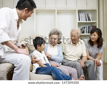 three-generation asian family talking in living room. - stock photo