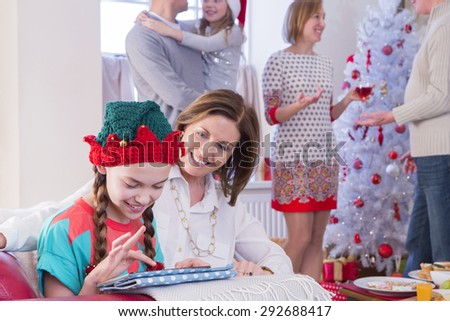 Three Generation Family at Christmas Time. A young girl and her grandma focus on the tablet while the rest of the family are socialising in the background.