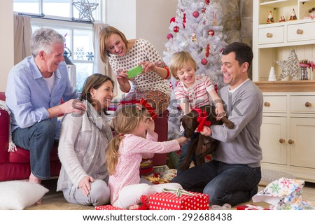 Three Generation Family at Christmas Time. Dad holds a small brown dog with a ribbon tied around its collar and everyone looks surprised. - stock photo