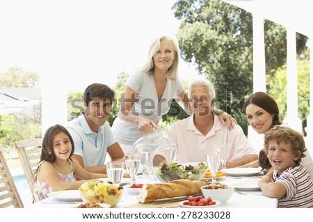 Three Generation Family Enjoying Meal Outdoors - stock photo