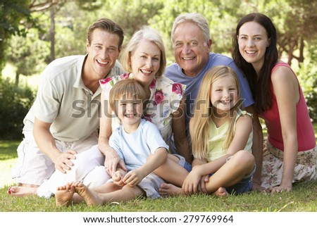 Three Generation Family Sitting In Park Together