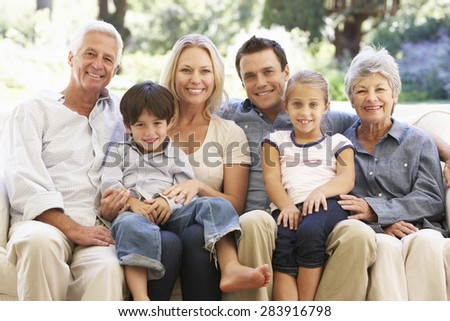 Three Generation Family Sitting On Sofa At Home - stock photo