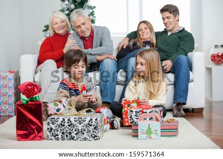 Three generation family with Christmas presents sitting at home - stock photo