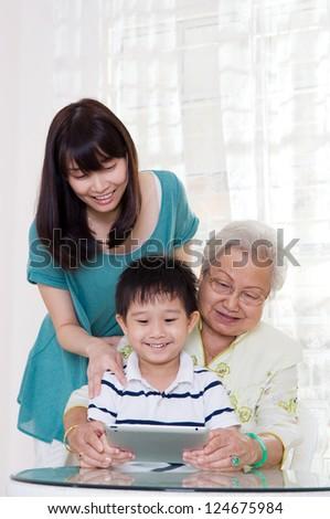 Three generations family having fun on the internet - stock photo