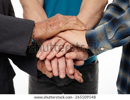 Three generations - grandfather, son and grandson holding hands, giving help and support each other - stock photo