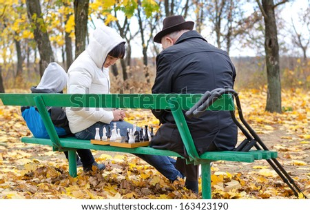 Three generations of a family playing chess with an elderly man and his daughter sitting on a park bench with the chessboard between them as his young grandson amuses himself playing on a tablet-pc - stock photo