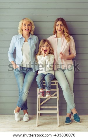 Three generations of beautiful women are looking at camera, showing surprise and smiling, standing against grey background - stock photo