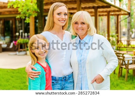 Three generations of happy women. Three generations of family women bonding to each other and smiling while standing in front of their house  - stock photo