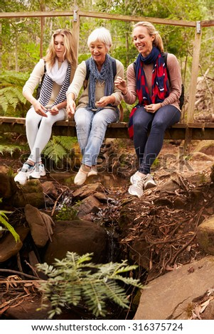 Three generations of women sitting on a bridge in a forest - stock photo