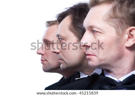 three gentlemen on a white background in black tuxedos - stock photo