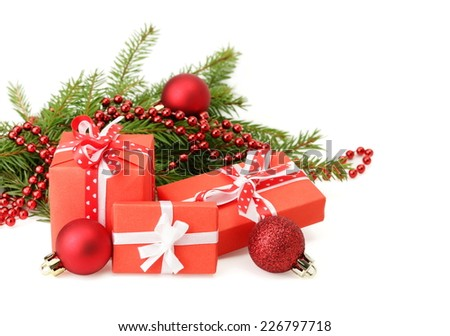 Three gift boxes with ribbon bows, Christmas tree branch and red balls on white - stock photo