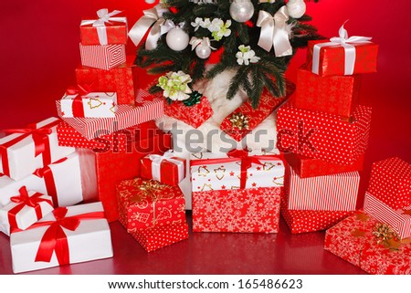 Three gift boxes wrapped with ribbons and bow isolated over red background