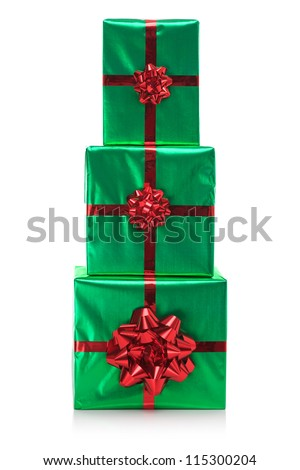 Three gift wrapped presents in green wrapping paper with red bow and ribbon, isolated on a white background. - stock photo