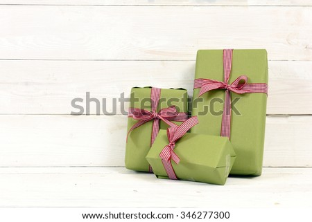 three gifts on white wooden background - stock photo