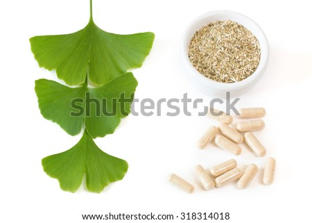 Three ginkgo leaves with dried herb and capsules over white background
