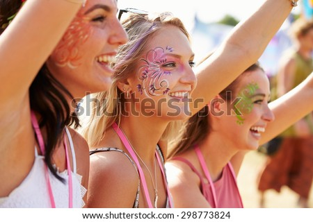 Three girl friends at a music festival, side view - stock photo