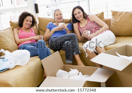 Three girl friends toasting champagne by boxes in new home smiling - stock photo